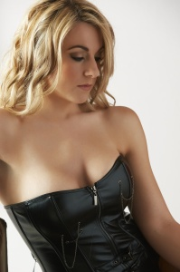 Sexy young Caucasian adult woman with soft curled blonde hair and a fuller figure in a light bedroom against a white wall, wearing a black leather corset